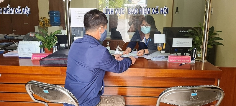 An employee submitting a dossier to settle the regime at the social insurance agency. Photo: Hai Duong Social Insurance (Photo taken before the pandemic occurred in this province)